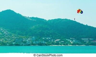 Tourist Parasailing behind Speedboat in Southern Thailand -...