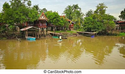 Elevated Houses along the Chao Phraya River in Thailand -...