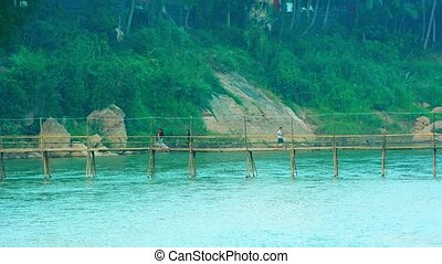 Villagers Crossing a Bamboo Bridge near Luang Prabang, Laos...