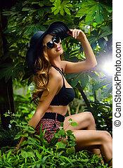 safari - Beautiful young woman among the tropical plants...