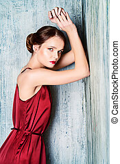 fashion - Sensual young lady in red dress posing an studio....