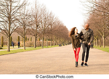 a young couple walking in the park