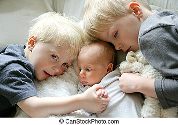 Big Brothers Hugging Newborn Baby Sister - Two young...
