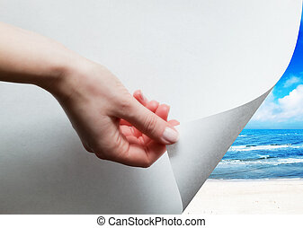 Hand pulling a paper corner to uncover, reveal sunny beach -...