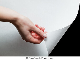 Hand pulling a paper corner to uncover, reveal something -...