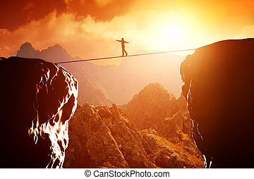 Man walking and balancing on rope over precipice in...