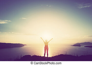 Happy woman with hands up on cliff over sea and islands at...