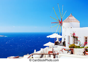 Famous windmills in Oia town on Santorini island, Greece -...