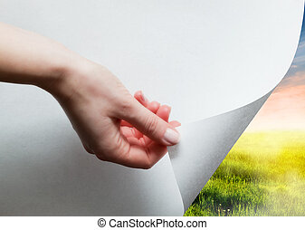 Hand pulling a paper corner to uncover, reveal green...