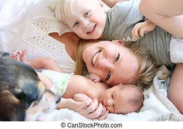 Happy Mother Laying in Bed with Toddler Son and Newborn Baby...