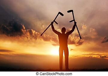 A disabled man raising his crutches at sunset. Medical...