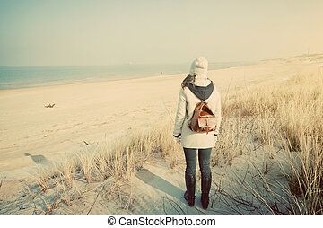 Woman with retro backpack on the beach looking at the sea -...