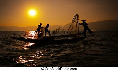 Silhouettes of fishermen at sunset. Ends fishing in the traditional way. Inle Lake, Myanmar