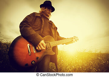Young man playing on the guitar outdoors. Vintage, music...
