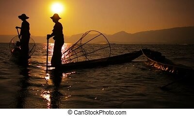 Silhouettes of fishermen at sunset. Vintage boats and fish traps. Inle Lake, Myanmar