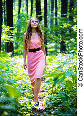 Young woman walking - Young woman in pink dress walking in a...