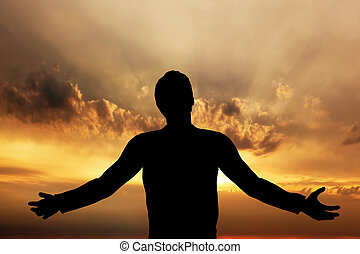 Man praying, meditating in harmony and peace at sunset...