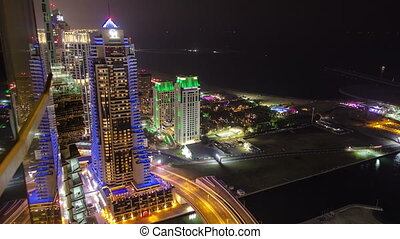 Dubai Marina at night view on hotels and bridge with traffic timelapse