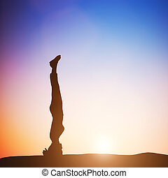 Woman in head stand yoga pose meditating at sunset Zen,...