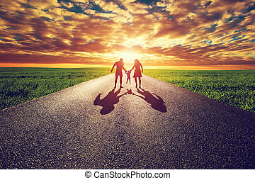 Family walk on long straight road, way towards sunset sun...