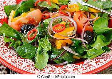 Raw salad with vegetables: spinach, tomatoes, olives, onion,...