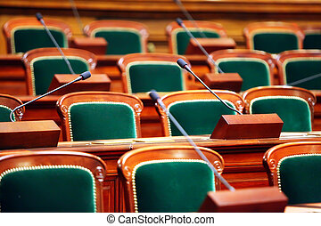 Empty vintage congress hall with seats and microphones.