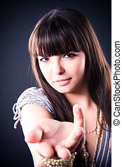 Young woman stretching hand. On dark background.