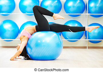 stretching exercises with fitness ball - woman doing...