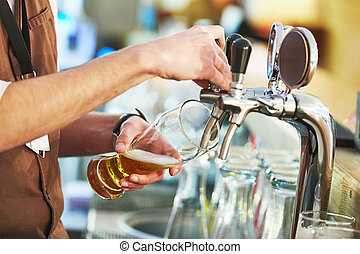 barman pouring beer - barman hand at beer tap pouring a...