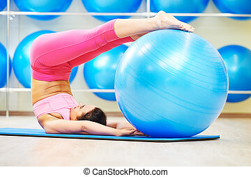 power pilates exercises with fitness ball - woman doing...