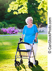 Senior lady with a walking aid in the park - Happy retired...