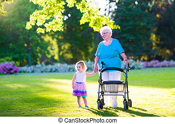 Grandmother with walker and little girl in a park - Happy...