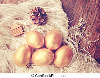 Gold easter eggs and decorated on wood background with retro...