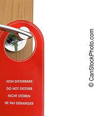do not disturb sign hanging on the door handle - closeup of...