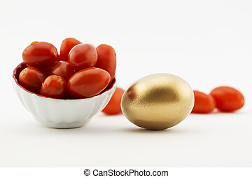 Gold egg with red tomatoes - Cherry tomatoes placed with...