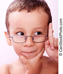 Child thinking - A boy with glasses, thinking and raising...