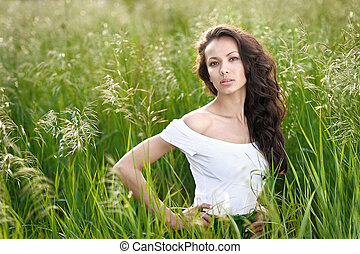 beautiful elegant brunette girl in a field