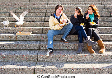 Eating fish and chips - Three young adults sitting on...