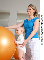 Baby standing at Physiotherapy beside a Fitness Ball - A...