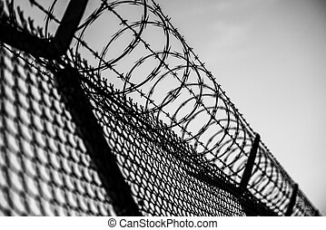 Prison Fence in Black and White. Barbed Wire Fence Closeup.