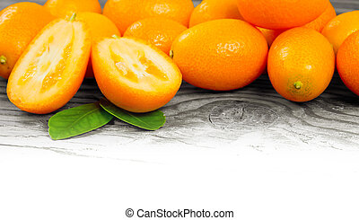 Kumquats - Photo of kumquats with slices and leaves on...