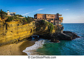 View of a house on a cliff and a small cove at Table Rock Beach,
