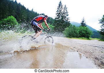wet mount bike ride - young man drive mountain bike over...