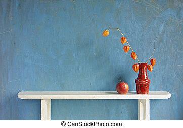 husk tomato plant flowers in vase on white wooden shelf -...