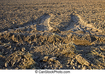 tractor traces on cultivated farm field soil