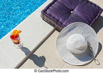 Luxury pool side shot of cocktail, hat and velvet cushion