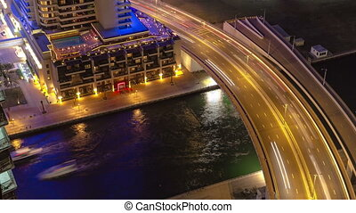 Dubai Marina at night view on river with boats and bridge with traffic timelapse near hotel