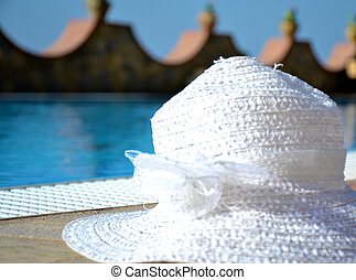 White straw hat female on poolside