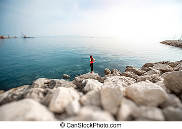 Woman on the rocky beach - Alone sport woman in red standing...