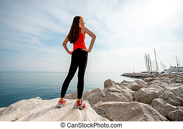 Sport woman on the rocky beach - Young sport woman in red...